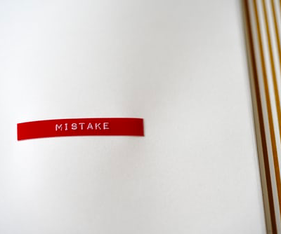 Mistake written on red tape on white paper