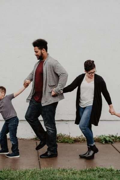 family hand in hand walking down sidewalk