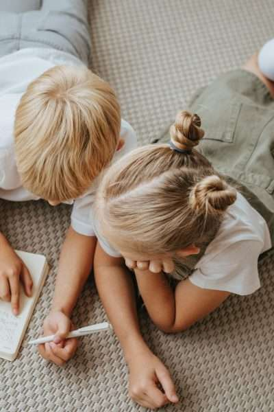 children writing while lying on floor