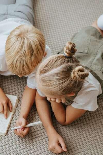 children writing while lying on floor