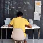 Boy sitting at desk below schedule on chalkboard