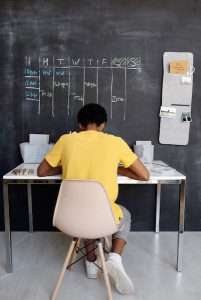 Boy sitting at desk below schedule on chalkboard