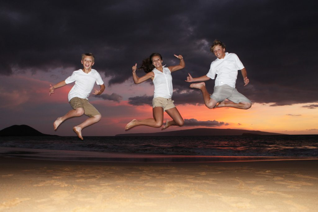 3 young adults jumping in the air on a beach