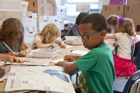 Boy at desk writing - attendance makes a difference