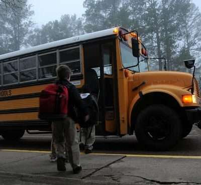 children boarding school bus - attendance makes a difference