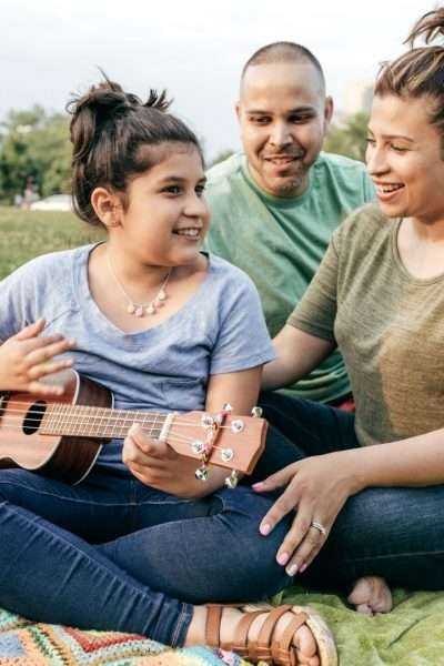 Mom, Dad and daughter sitting on ground, girl playing ukulele