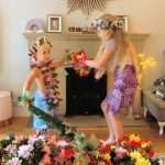Girl and boy dressed in Hawaiian dance costumes, playing pretend