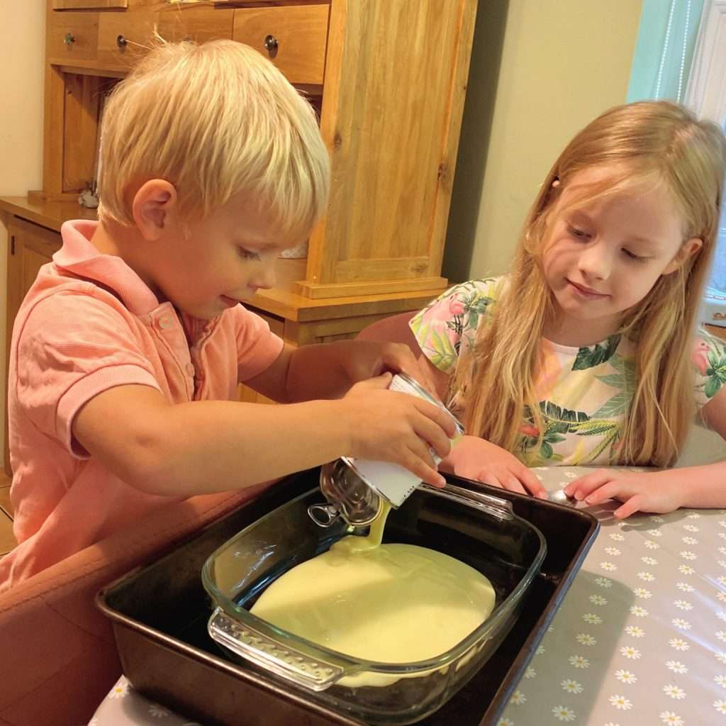 boy and girl pouring liquid into baking pan