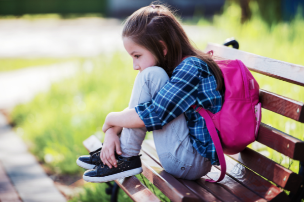 Anxious Girl on bench with backpack