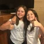 two girls with thumbs up by TV- kids summer movie suggestions