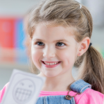 girl smiling at adult holding a smiling face drawing, character education