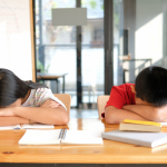 boy and girl with head down on textbooks, school is tough